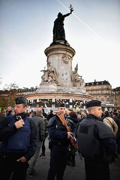 Armed police patrol at Place de la Republique as France observes three days of national mourning for the victims of the terror attacks on November 15...