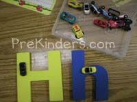 Letter Roads I have a box of mini toy cars and large foam letters from Lakeshore. Children practice letter formation by driving the cars aro...