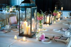 Centerpieces - no vases between lanterns, arrange flowers around lanterns with petals and (possibly) confetti made from play book scattered between.