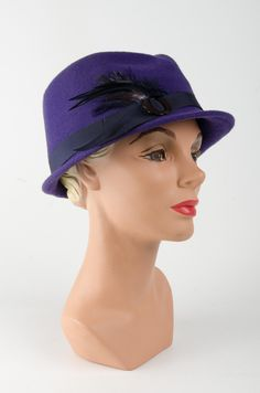 This cute little trilby hat goes by the name Jean. With its simple asymmetric brim dropping to the right-side of the slanted crown and its jaunty feather detailing, this hat really does stand out from the crowd. Fitted with a petersham ribbon on the inside for ultimate comfort and trimmed with a thick band, feather and vintage buckle. Colour: Bright purple with dark grey band, feather and brown buckle. #Fabhatrix #Edinburgh #Grassmarket #Jean #formedfelt #hat Trilby Hat, Bright Purple, Felt Hat, Edinburgh, Dark Grey, Headpiece, Crowd, Feather, Ribbon