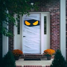Spooky front door decorations signals trick or treaters to stop by your house. Easy to do with a bit of yellow construction paper and toilet paper.