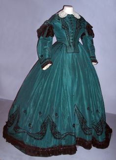 "Day Dress (bodice and skirt) 1863-65. ""During this period the wide skirt was fashionable. The fullness of the skirt had receded towards the back of the garment creating a flatter front. Women had crinoline petticoats made of steel hopes under their dresses to give the required shape. Lightweight fabrics (silk and muslin) were popular. This gown is silk with hand embroidery in black silk with black taffeta and a lace collar."" Victoria and Albert museum."