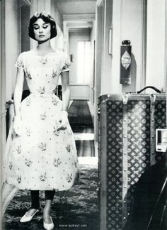 "Audrey Hepburn standing next to a giant Louis Vuitton suitcase in ""Love in the Afternoon"""