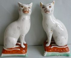 PAIR-LATE-19THC-STAFFORDSHIRE-CATS-ON-ORANGE-AND-GREEN-CUSHIONED-BASES