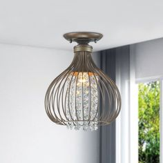 Create a fresh look for almost any room in your home by bathing the space in the illumination provided by this crystal semi flush mount. The piece features a cage-style design that enclose multiple crystal beads to gently diffuse the light and deliver an antique appearance. The flush-mount fits neatly against the ceiling, reducing the amount of additional clearance needed for safe hanging overhead. The intricate design of the jewels inside the copper cage makes for a very unique and…
