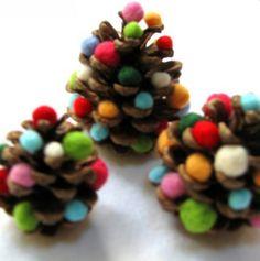 Kleine kerstboompjes van een denneappel en kleine bolletjes.