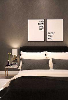 Um quarto de casal moderno e minimalista, onde o preto e o branco são as cores principais; destaque para a parede de cimento queimado e a luminária de parede