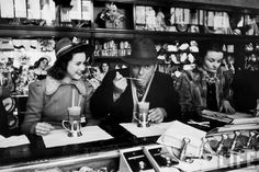 Actress Deanna Durbin having an ice cream soda at a counter with entertainer Eddie Cantor, New York City, 1938.