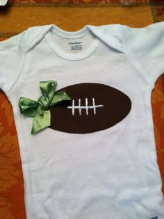 Football onesie with team colored ribbon bow, maybe add a tutu skirt for ultra extra cuteness!!