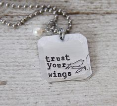 Be brave! Give in and trust your wings! This sweet message is hand stamped along with our exclusive bird into a thick metal square.  It's been hammered on the edges for a fun rustic texture. The pendant is about 1