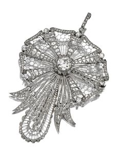 DIAMOND PENDANT-BROOCH, CIRCA 1910.  The pierced stylized ribbon medallion set in the center with an old European-cut diamond weighing approximately 1.50 carats, further decorated with small old European-cut and rose-cut diamonds, mounted in platinum, brooch fitting detachable.