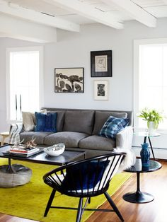 Great colours in this room with white walls, grey lounge, chartruese rug and black accessories