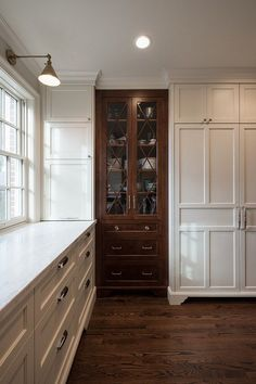 cabinet is stained Alder-Elizabeth Kimberly Design. Northstar Builders, Inc. Love the brown cabinet to break up the white cabinetry.