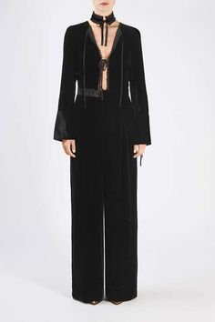 Invest in a one-of-a-kind piece this season with this velvet style jumpsuit by Unique. In a sleek black, it features an intricate cut-out plunge design to the top with pretty ruffle edge and lace up detail. With elongated sleeves and trousers for a dramatic finish.