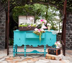 Love this aqua vintage dresser with old suitcases and flowers!