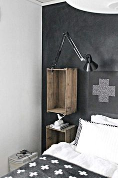 """Dark, serene colors in a Nordic bedroom design. The blanket looks a lot like Pia Wallén's """"Cross Blanket,"""" although hers is reversible. If the design is too bold for your tastes, though, Yllefabrik makes a similar """"Cross Wool Throw"""" in grey and black variants, with softer colors and smaller crosses."""