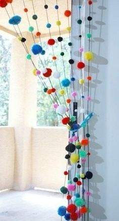 I can't read spanish but love the picture of this drape made of pompon's.