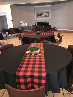 Lumberjack themed baby shower. Black table clothes, flannel table runners, wooden circle cut with mason jar, tea light candle and greenery.