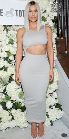 Kim Kardashian showed off her toned abs in a body-hugging dress that nearly matched her platinum blonde, new lob. Staying true to her signature look, she kept accessories to a minimum and finished off the outfit with nude heels