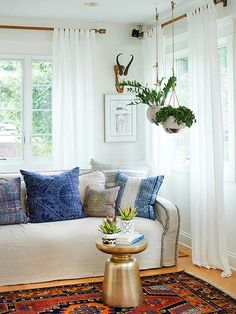 Because Bohemian style is so eclectic, it's easy for it to venture into chaotic territory. One way to rein it in is with a cohesive, complementary color palette. In this sunny living room, an orange-and-blue oriental rug grounds the space and provides color palette inspiration for pillows and other decorative items./