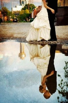 Reflection of bride and groom kissing