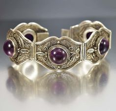Large natural amethyst gemstone cabochons in a silver filigree are the focal point of this superb early 19th century Art Deco antique Chinese bracelet. Five slightly curved links of filigree with scal
