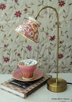 ~take an old reading light, remove the cover, drill a hold on the bottom of a lovely tea cup, and add as a shade, adorable~