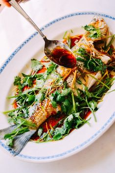 A steamed whole fish is a favorite on any Chinese table. This Cantonese steamed fish recipe with soy, scallion and ginger a a must-try fish recipe. The tutorial on how to serve a Chinese steamed whole fish at the table is one-of-a-kind!