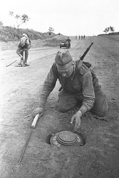 Soviet soldiers uncover and neutralize Tellermine 43 anti-tank mines planted in the road by retreating German Wehrmacht Engineers following the Battle of Kursk. The metal probe was used to identify any sign of buried mines. Near Kursk Kursk Oblast Russia Soviet Union August 1943.