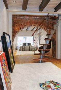staircaise + exposed brick arch + wooden floors + timber frame + area rug = my kinda house