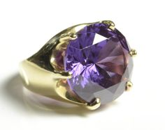 SYNTHETIC ALEXANDRITE AND FOURTEEN KARAT GOLD RING, with six yellow gold prongs securing a round-cut synthetic alexandrite weighing approximately 17.17 cts. Ring size: 5-1/2. Estimated to sell between $300-400. To be sold as lot 0214-0113.