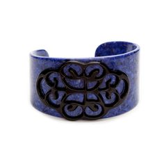 "The vibrant lapis Chelsea cuff adds a quick pop of color to any ensemble, with bold blue contrasting perfectly against Chelsea's raised black filigree design. This tapered cuff will combine perfectly with bangles for a little punk rock flair.   - Resin  - 3"" wide"