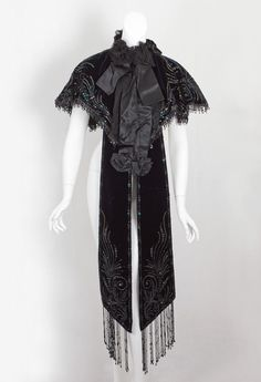 Beaded velvet capelet attributed to Doucet, c.1898. For Jacques Doucet, a garment had to be theatrical—grand, luxe, and gala. Lavishly embellished with iridescent sequins and novelty paillettes, the dazzling design is accented with black pleated chiffon ruffles in front and with black chiffon rosettes around the neckline.