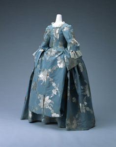 The feature of the dress, or mantua, is the long train extended at the back. Both sides of the overskirt were drawn back over the hips, with the train worn in different styles. One style was for the train to be pulled long as a way of showing off the sumptuous textle. Alternatively, as in the photograph, the train was folded over and attached at the waist. The sides of the train were double-sided so that only the proper face, and not the reverse, of the textile was visible when worn with the ...