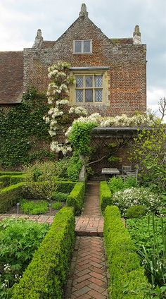 White English Garden, love the brick pathway and climbing wisteria
