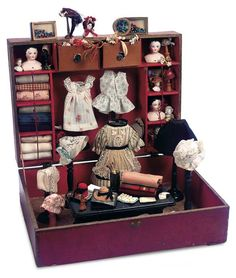 French Toy Boxed Seamstress Set Labeled 14 (36 cm.) x 14. A wooden box with red and gilt paper cover and gilt-lettered labelLingerie hinges open to a well-fitted interior depicting a seamstress shop. French,circa 1885
