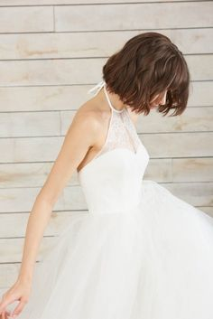 Chantilly lace scallops are delicately placed to create beautiful illusion on this modern halter ball gown. A structured sweetheart bodice defines the bust and offers striking contrast to a full, layered skirt of tulle and horsehair.