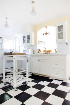 love the big black and white square tiles and the rolling kitchen island