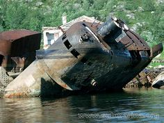 This is one of many abandoned Russian submarines near the Arctic. When the Russians get tired of their ships they tie them up somewhere and walk away. Many, many nuclear submarines like this lie half or fully sunk at rotting docks contaminating acres around them with radiation. Very little security is provided and anyone can go aboard, although this is treacherous due to no lights and vandals and scavengers stripping them. Radioactive surplus is often found on the market in Russia.