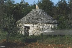 Stock Photo : Round stone house with conical roof, set within and partly overgrown by shrubs and trees, blue sky visible in background.