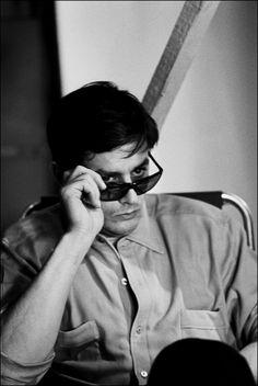 Alain Delon peering over his sunglasses.