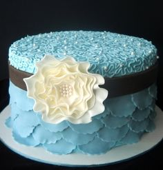 Beautiful blue cake with cornelli lace, pearls, scalloping and a stylised sugar flower brooch.