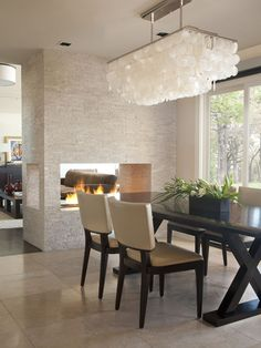 Tear down wall and French doors between formal living space and dining, put in fireplace as a room divider.