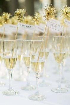 Champagne flutes were filled and embellished with gold pompom toothpicks, with guests' names and table assignments written on them.