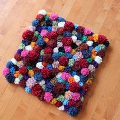 Make your own fun and funky pompom accent rug- sure to liven up the living room.