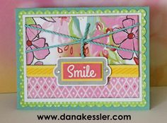 "May 2015 SOTM Just Sayin' Blossom Smile Card ~ ""I did a little tone on tone stamping with the striped pennant stamp on the canary strip – love how this really adds another layer!   I also stamped the tag image in whisper ink and hand trimmed it out.  The ""Smile"" was cut out from our new Carnival Washi Tape."""