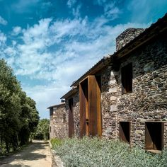 Rusted steel window and door frames project from stone and plaster walls of this renovated farm house in Spain's Gavarres mountains by Zest Architecture.