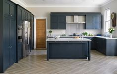 Dark blue-grey kitchen design for Esher, Surrey home. With parquet flooring and large island with storage.