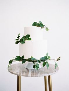 Simple two tiered white wedding cake with green vines. A minimalist wedding cake design with deep jewel tone palette. #minimalistwedding #minimalistweddingcake #minimalistweddingideas