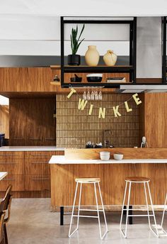 A Modernist Palm Springs-style home in Byron Bay. The kitchen features timber tones paired with concrete flooring and amber tiles.